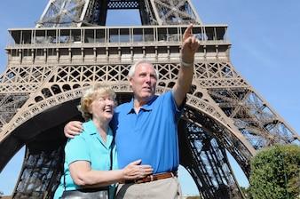 Senior Mann neben dem Eiffelturm bei etwas zu seiner Frau zeigen