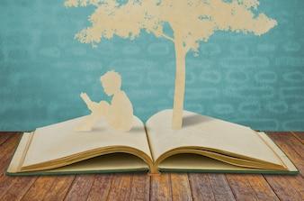 Silhouetten von einem Baum und ein Mann, der auf einem Buch