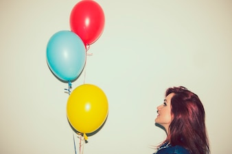 Smiely junge Frau Blick auf Ballons
