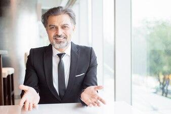 Smiling Business Leader Gestikulieren am leeren Schreibtisch
