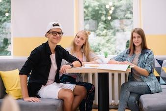Smiling Teens mit Lehrbüchern im Cafe