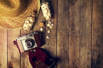 Sommer- oder Urlaubskonzept. Strohhut mit alten Vintage-Kamera und Muscheln auf lebendigen Hintergrund. Draufsicht