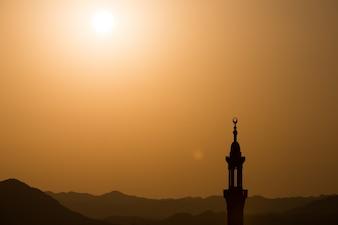 Sonnenuntergang über Wüste mit moslemischen Moschee im Vordergrund