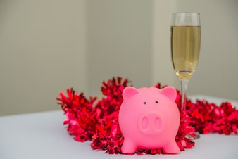 Sparschwein mit Weihnachtsschmuck. Sparschwein mit einem Glas Champagner und Neujahrsschmuck