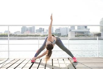 Sportliche Frau üben Yoga am Stadtkai