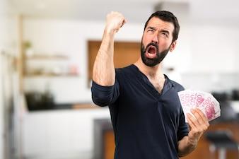 Stattlicher Mann mit Bart, der viel Geld im Haus nimmt