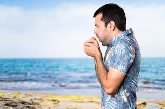 Stattlicher Mann mit Blumenhemd hustet viel am Strand