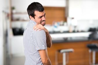 Stattlicher Mann mit Schulterschmerzen im Haus