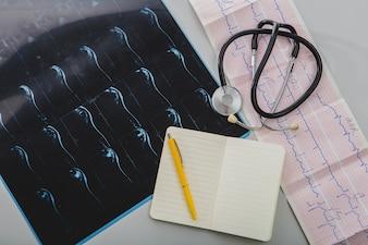 Stethoskop mit Notizblock und Röntgenaufnahme