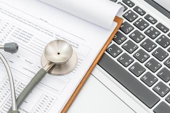 Stethoskop und Rezept auf dem Laptop