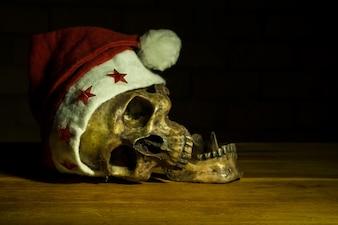 Stilleben mit Schädel am Weihnachtstag, dunkles Konzept