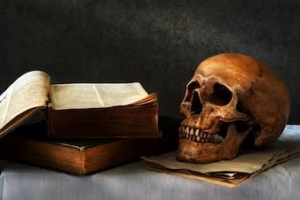 Stillleben Kunst Fotografie auf menschlichen Schädel Skelett mit Buch omn Schreibtisch