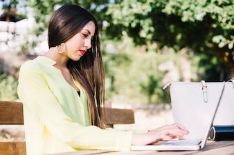Stilvolle Frau mit Laptop im Park