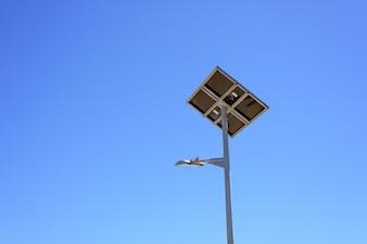 Straßenlaterne mit Sonnenkollektor auf blauem Himmel Hintergrund. Grüne Energie.