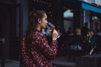 Stylish junge Mädchen trinkt Wein in einem Straßencafé auf einer Sommerterrasse. Ein Mädchen mit langen Haaren genießt ein Glas Wein an einem Sommerabend. Porträt. Nahansicht
