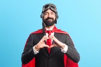 Super Held Geschäftsmann ein Herz mit seinen Händen auf bunten Hintergrund
