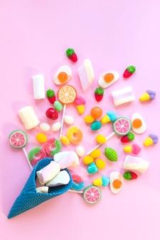 Süßigkeiten auf rosa Tisch verstreut