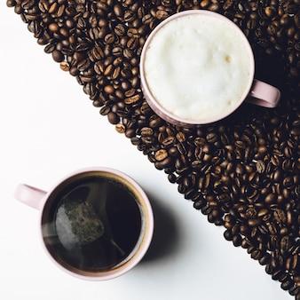 Tasse Kaffee steht auf weißem Tisch und Tasse Milch auf dem Tisch mit Kaffee Körner bedeckt