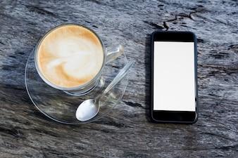 Tasse Kaffee und Smartphone auf Holztisch