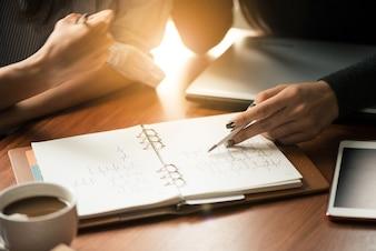 Teamarbeitsprozess Junge Geschäftsführer-Besatzung mit neuem Startup-Projekt. Labtop auf Holztisch, tippende Tastatur, Texting Nachricht, analysieren Grafikpläne. Objektiv Flare.