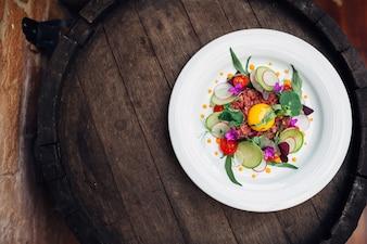Teller mit frischem Salat auf Holzfass