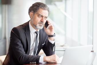 Tensed Business Man Sprechen am Telefon am Schreibtisch