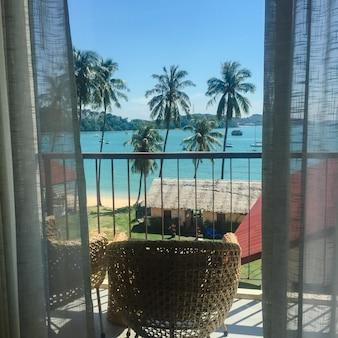 Terrassenlounge mit Rattansessel und Meerblick in einem Luxusresort. Sommerurlaubskonzept