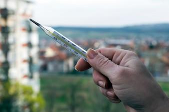 Thermometer in einer Frau Hand. Temperaturmessung durch ein Thermometer. Fieber messen