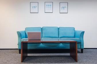 Tisch mit Laptop-Sofa stehen im Zimmer