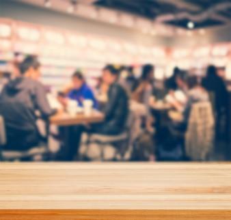 Tischtisch mit verschwommenem Coffee Shop - gut für die Gegenwart und Produkte zu fördern.
