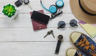 Top-Ansicht Zubehör zu Reise-Konzept. Handy hören Musik von Kopfhörer auf hölzernen background.shoes, Pass, Uhr, Sonnenbrille und Hut auf Holz Tisch.