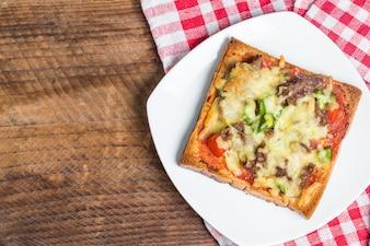 Top Blick auf Toast mit Käse und grünem Pfeffer