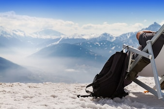 Tourist Chilling Sitzplätze in Chaiselongue Sonnenbank auf Berg Hintergrund, Schnee. Horizontal. Text kopieren Tourismus Winter Konzept.