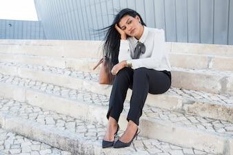 Traurige langweilige Geschäftsfrau, die auf Treppen sitzt