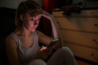 Trauriges und mürrisches Teenager-Mädchen, das Nachricht auf ihrem intelligenten Handy sendet