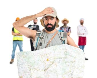 Überrascht Backpacker mit Karte auf weißem Hintergrund