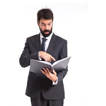 Überrascht Geschäftsmann liest ein Buch über weißem Hintergrund