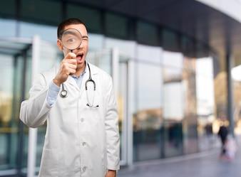 Überraschter junger Arzt mit einer Lupe