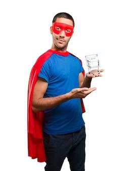Überraschter Superheld mit einem Einkaufswagen