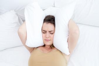 Unzufriedene Dame, die Ohren mit Kissen im Bett bedeckt