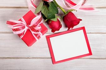 Valentine Geschenk-Box und leere Karte auf einem Holzbrett