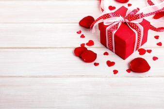 Valentine Geschenk-Box und Rosenblätter auf dem weißen Holzbrett