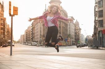 Vergnügte junge Frau springt auf Bürgersteig