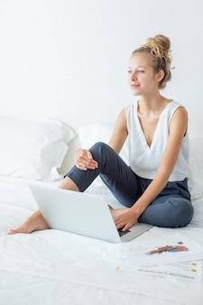 Verträumte hübsche Frau, die an Laptop auf Bett arbeitet