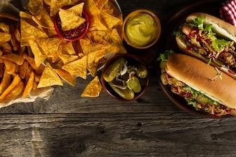 Vielzahl von klassischen traditionellen amerikanischen leckeren Junk ungesunde Lebensmittel auf hölzernen Hintergrund mit Kopie Raum. Hot Dogs und Chips.