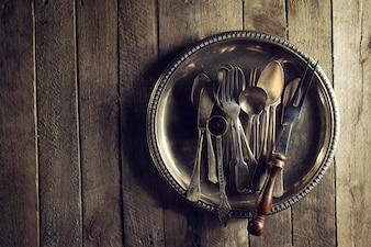 Vintage Old Rustic Küchenutensilien Gabeln Löffel und Messer auf Old Wooden Table. Essen oder Vintage Rustikales Konzept. Draufsicht.