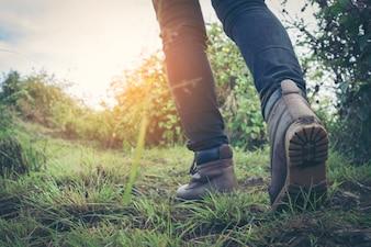 Wanderer, der auf Berg bei regnerischem Wetter geht. Ansicht der Beine