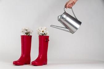 Wasser Stiefel neben einer Hand mit einer Gießkanne