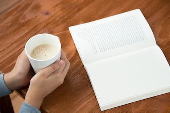 Weibliche Hände halten Kaffeetasse auf Tisch mit Buch