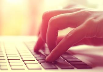Weibliche Hände tippen auf Laptop mit Aufflackern Licht